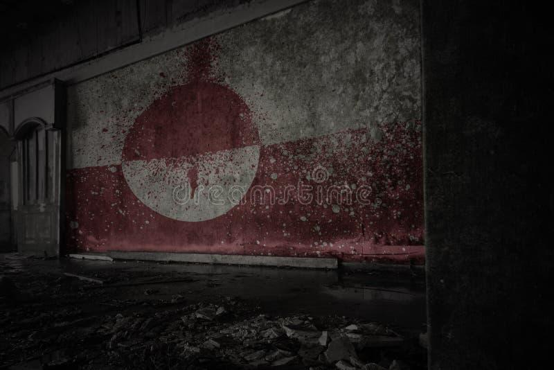 格陵兰的被绘的旗子在肮脏的老墙壁上的在一个被放弃的被破坏的房子里 库存图片