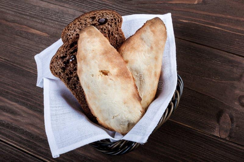 格鲁吉亚lavash,新鲜的皮塔饼面包,在篮子的麦子小面包干在木背景 免版税库存照片