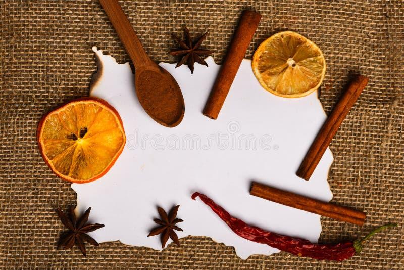 桂香、干桔子和胡椒,在白纸附近的八角食谱的,拷贝空间 纸在麻袋布的 图库摄影
