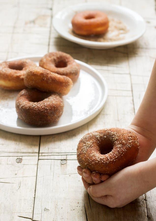 桂香油炸圈饼对于儿童手和在一张木桌上 免版税库存照片