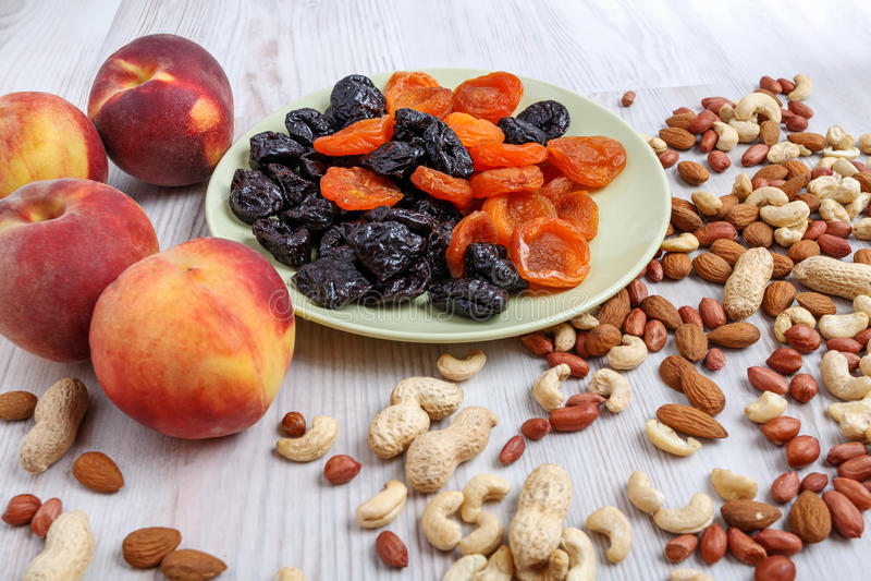 桃子、坚果和板材用杏干和修剪在桌上 免版税库存图片