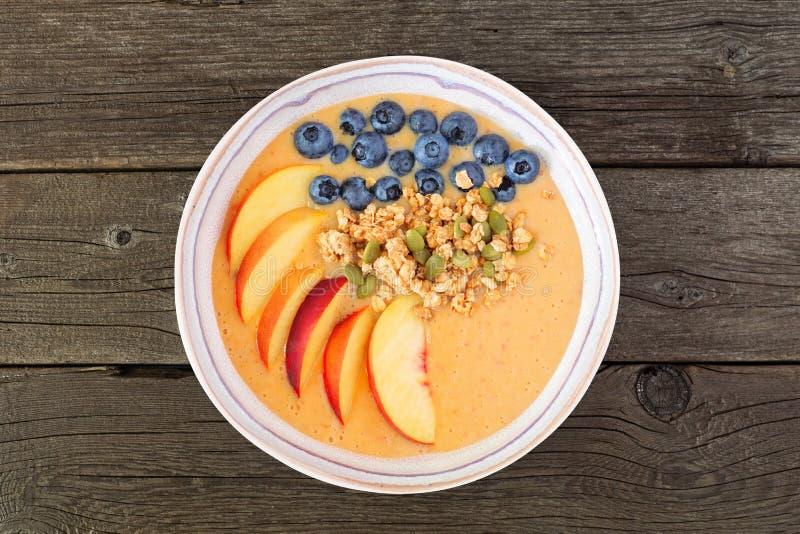 桃子圆滑的人碗用蓝莓和格兰诺拉麦片,在黑暗的木头的顶视图 免版税图库摄影