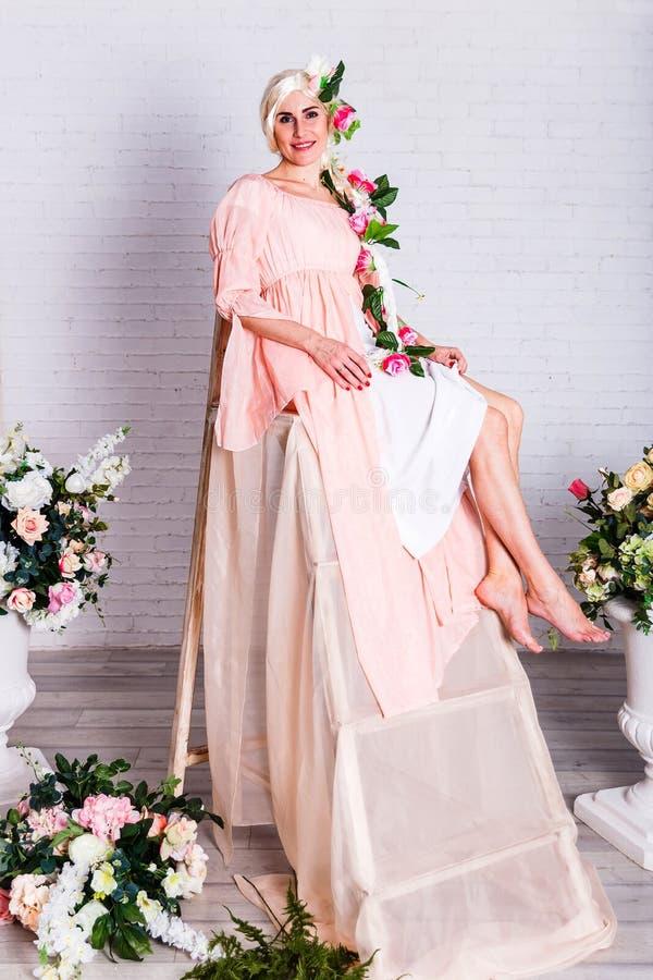 桃子宽松礼服和一顶白色假发的一白种人年轻女人坐高的步 做人造花 免版税库存照片