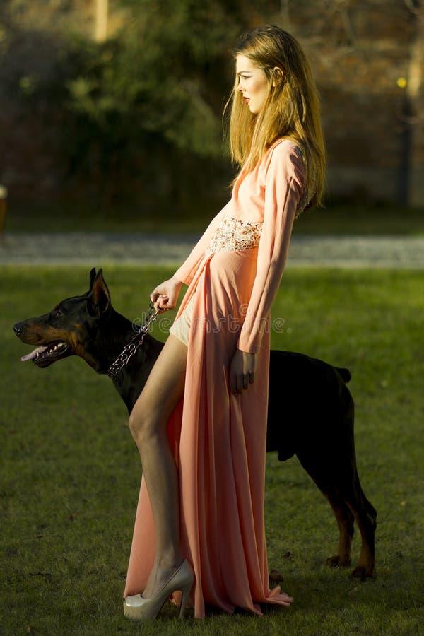 桃子礼服的俏丽的妇女有大型猛犬的 免版税库存照片