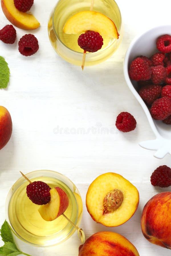桃子酒和果子在白色木桌上 图库摄影