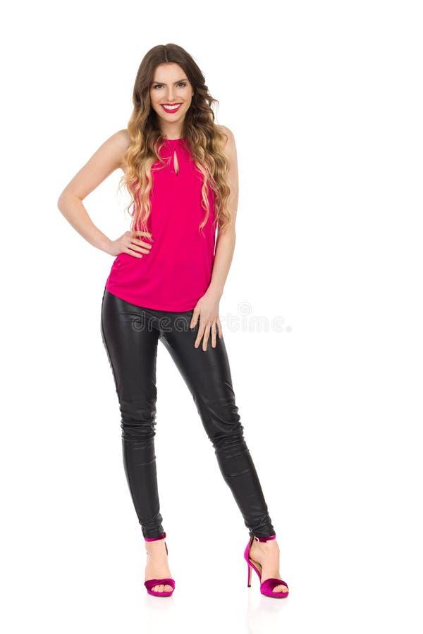 桃红色上面、皮革长裤和高跟鞋的微笑的美女 免版税库存图片