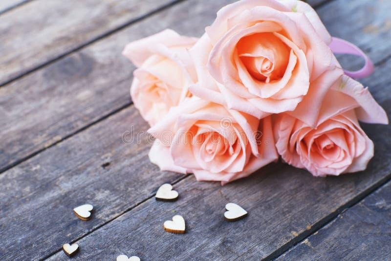 桃红色丝带和微型心脏形象栓的可爱的软的橙色粉色玫瑰装饰在木桌背景,甜华伦泰 免版税图库摄影