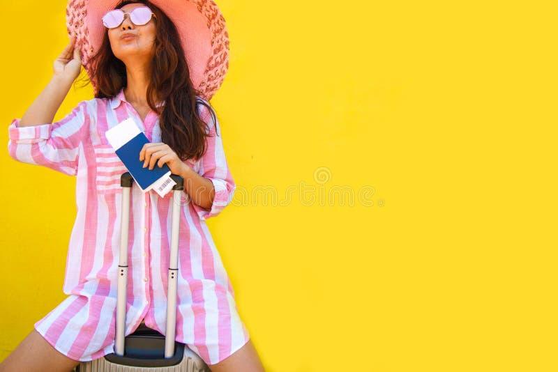 桃红色举行的手提箱的,护照在黄色背景隔绝的登机牌票愉快的极度高兴的年轻女人 库存照片