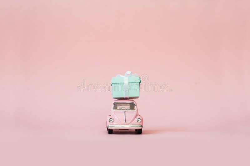 桃红色交付礼物盒的玩具减速火箭的模型汽车为华伦泰在桃红色背景的` s天 在桃红色背景的大众甲壳虫 库存图片