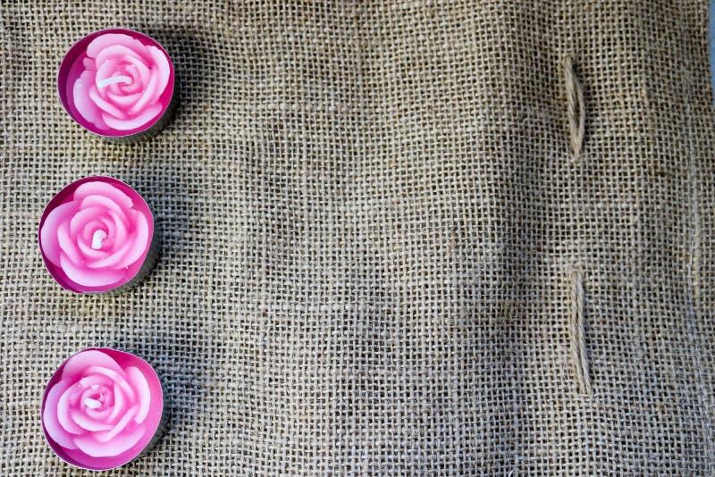 桃红色以玫瑰色花的形式蜡美好的蜡烛与在一块老棕色帆布的背景,苛刻, unbl的一个未成熟的灯芯 库存图片