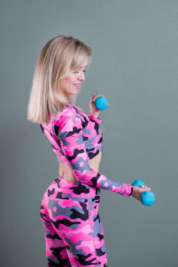 桃红色伪装运动服的美丽的白肤金发的女孩做与哑铃的锻炼 二头肌锻炼 四分之三长度 库存照片