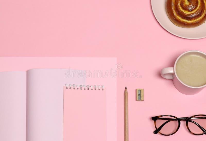 桃红色便条纸,木铅笔,磨削器,咖啡杯,在桃红色背景的蛋糕 库存图片