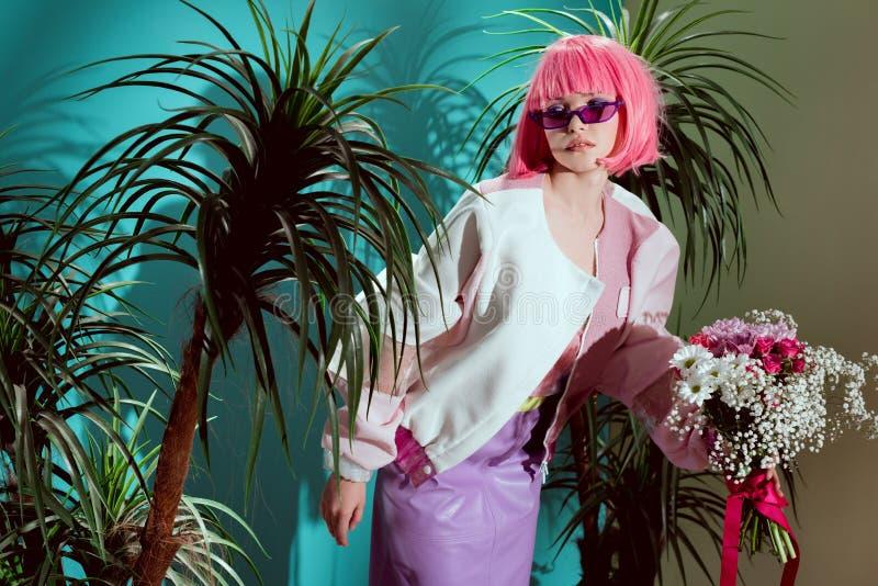 桃红色假发藏品花束和摆在的美丽的时兴的年轻女人之间 库存照片