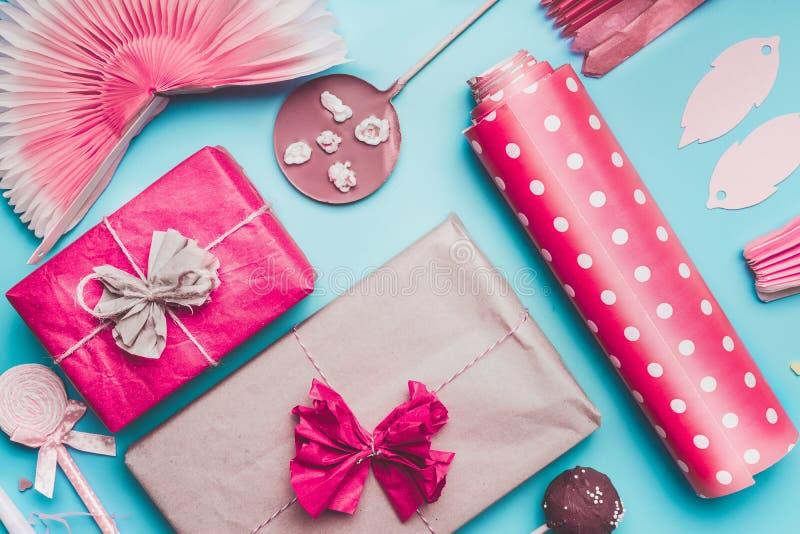 桃红色党问候设置与礼物盒、包装纸、装饰和巧克力蛋糕流行音乐在蓝色背景,顶视图 r 库存图片