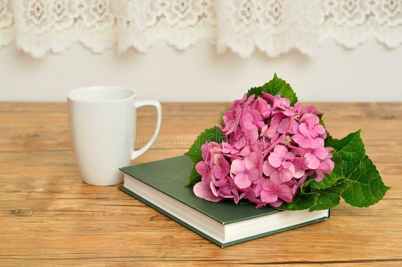 桃红色八仙花属、一本绿色故事书和杯子 免版税库存图片