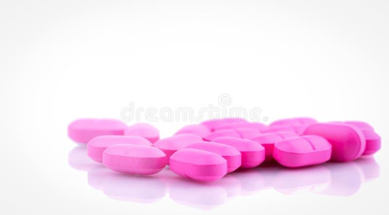桃红色压片在白色背景隔绝的药片 治疗膀胱炎的诺氟沙星400毫克 抗菌药抵抗 背景药片桃红色纹理 免版税库存照片