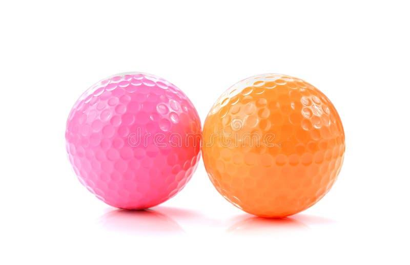 桃红色和橙色小小高尔夫球球在白色背景 免版税图库摄影