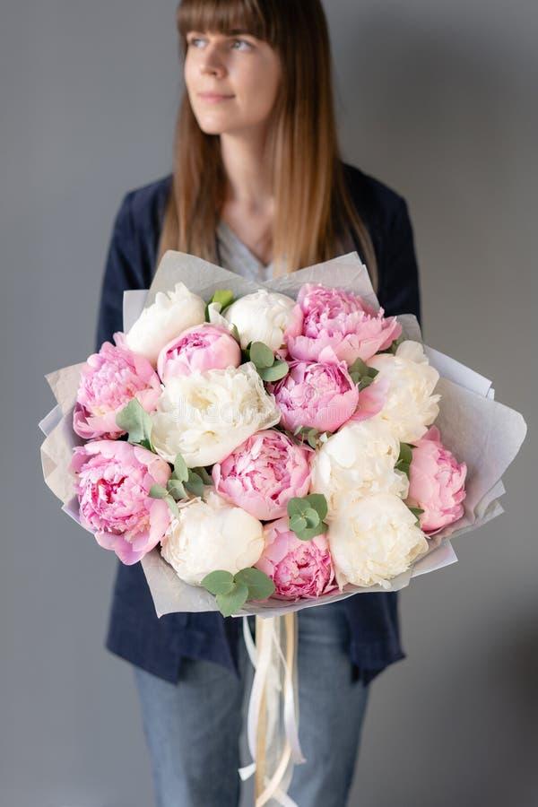 桃红色和白色牡丹在妇女手上 编目或网络商店的美丽的牡丹花 花卉商店概念 免版税库存照片