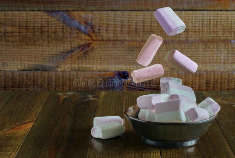 桃红色和白色蛋白软糖在一个黑色的盘子任意地落,在一张木桌上站立 库存照片