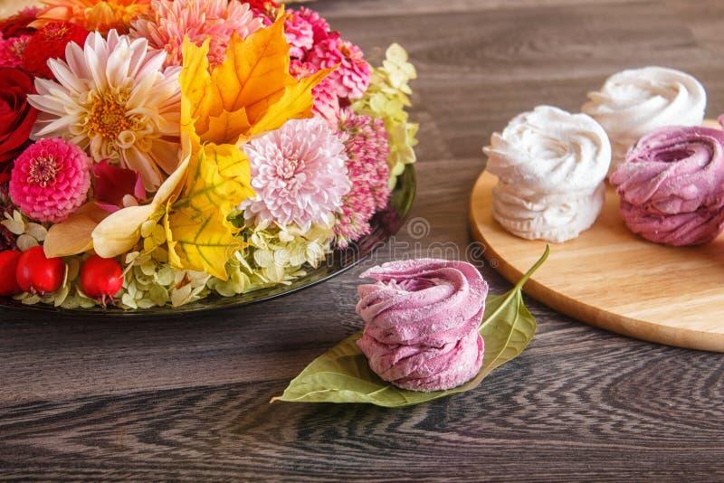 桃红色和白色蛋白软糖过眼云烟在一个圆的木板wi 免版税库存图片