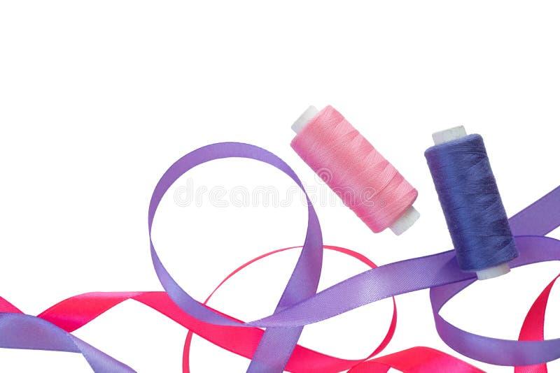 桃红色和紫色卷曲桃红色缎带、短管轴和在白色的紫色螺纹 与两缎带的水平的横幅和 免版税库存照片