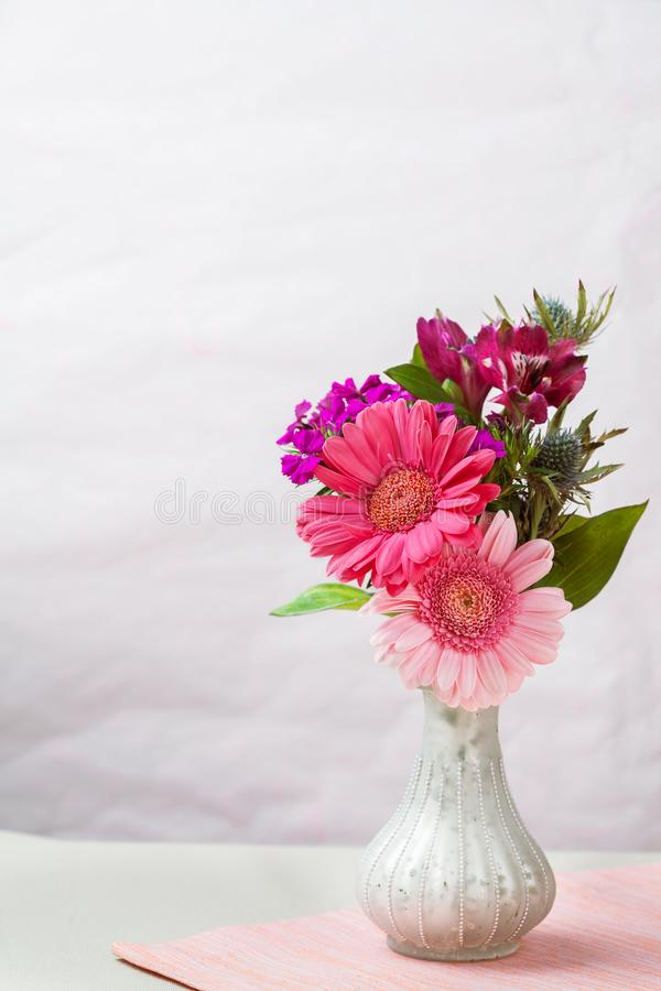 桃红色和紫色花在花瓶 库存照片