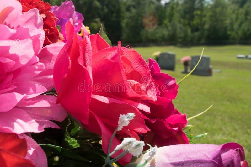 桃红色和红色织品花在公墓 免版税库存图片