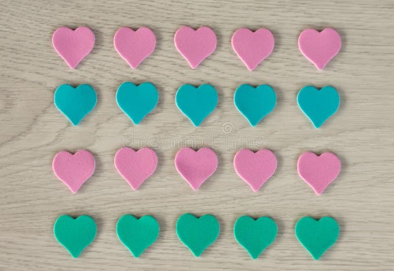 桃红色和蓝色谎言的小心脏在一张白色木桌上的 免版税图库摄影