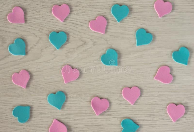 桃红色和蓝色谎言的小心脏在一张白色木桌上的 库存照片