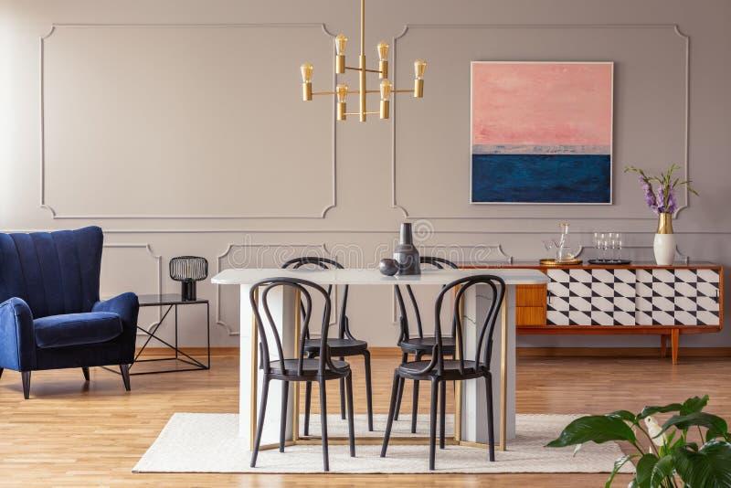 桃红色和藏青色在一个典雅的用餐和客厅提取在灰色墙壁上的绘画有造型的 图库摄影