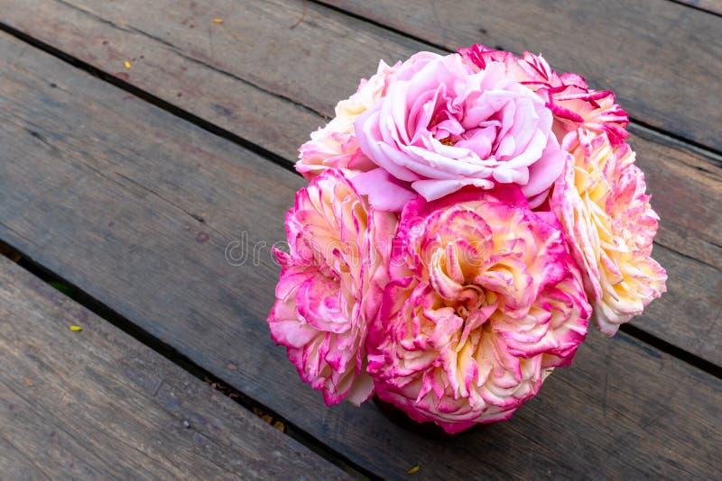 桃红色和黄色玫瑰花束在花瓶坐棕色木板条地板 免版税库存图片
