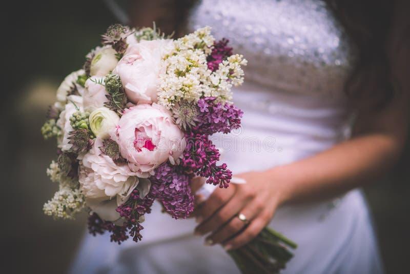 桃红色和紫色婚礼花束在新娘手、婚礼之日、婚礼与牡丹和丁香上 免版税库存照片