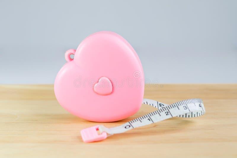 桃红色在木头的心脏测量的磁带 库存图片