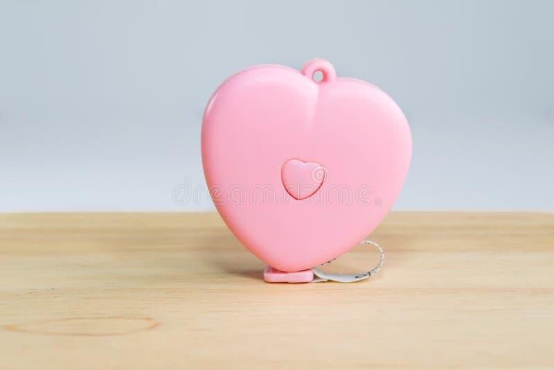 桃红色在木头的心脏测量的磁带 免版税库存照片