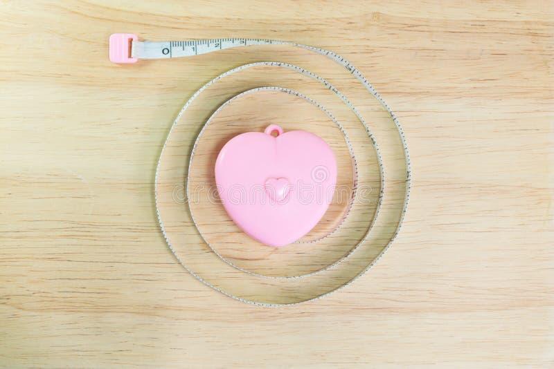桃红色在木头的心脏测量的磁带 免版税库存图片