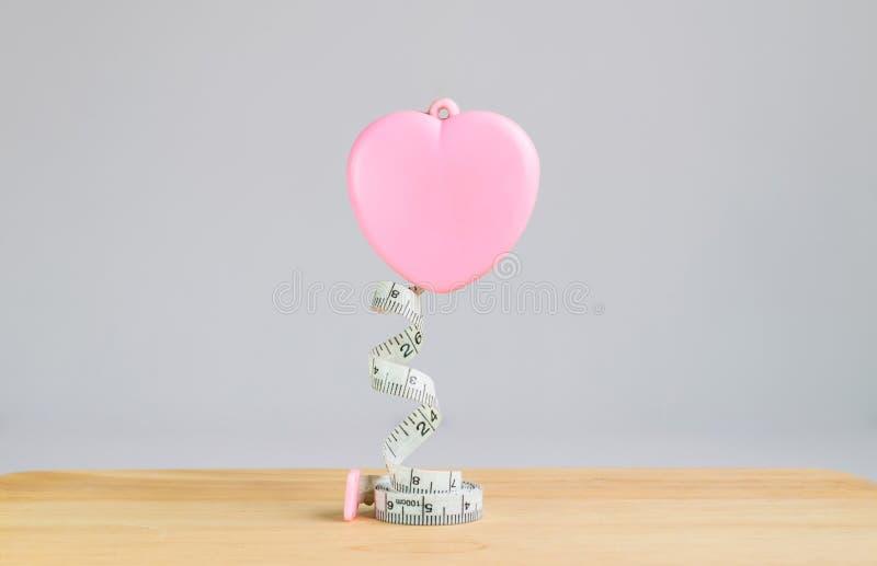 桃红色在白色背景的心脏测量的磁带 免版税库存照片