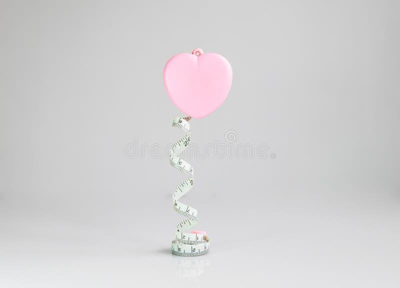 桃红色在白色背景的心脏测量的磁带 免版税库存图片