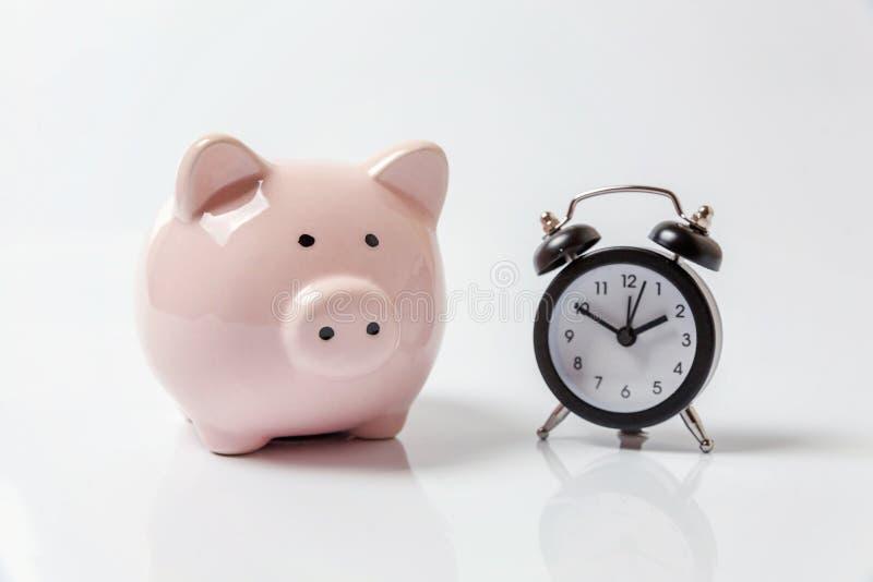 桃红色在白色背景隔绝的存钱罐和经典闹钟 免版税图库摄影