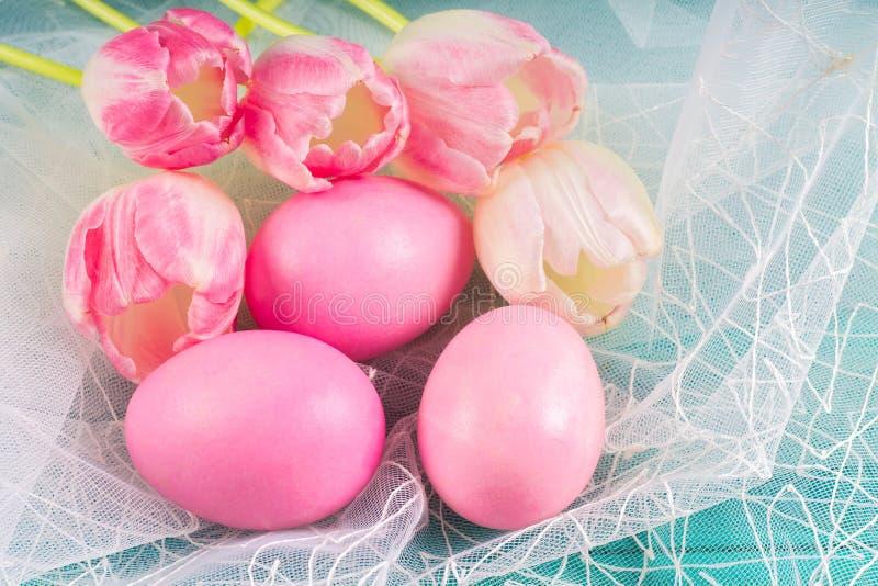 桃红色复活节彩蛋和郁金香在白色织品和蓝色木背景 免版税库存图片