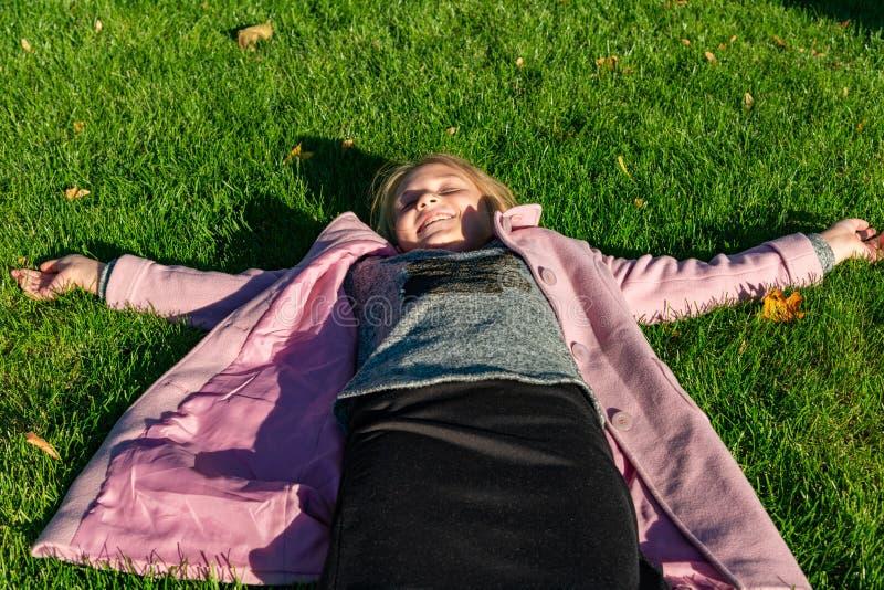 桃红色外套的女孩在绿草在秋天说谎在公园 库存照片