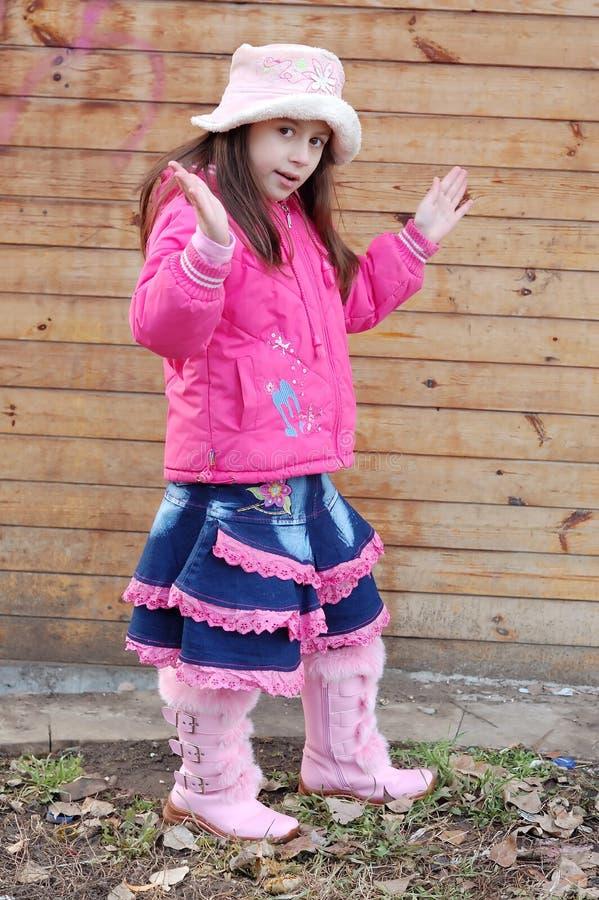 桃红色外套的逗人喜爱的女孩 免版税库存图片