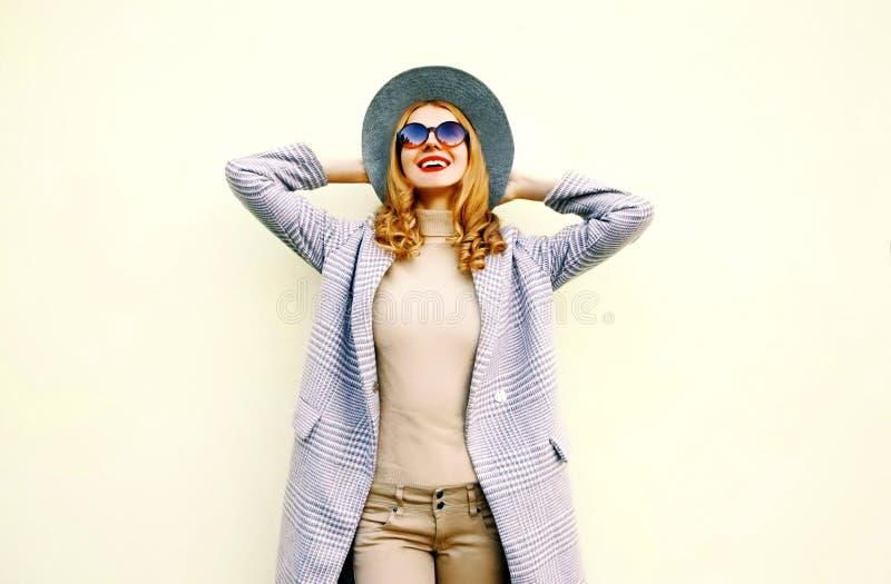 桃红色外套的,圆的帽子美丽的愉快的年轻微笑的妇女 免版税库存图片