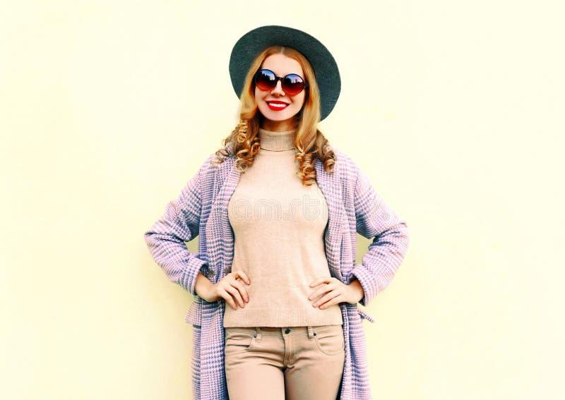 桃红色外套的,摆在背景的圆的帽子画象俏丽的微笑的妇女 库存照片