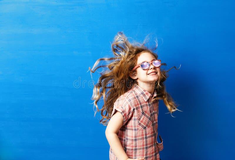 桃红色太阳镜的愉快的儿童女孩游人在蓝色墙壁 旅行和冒险概念 免版税图库摄影