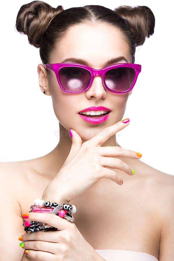桃红色太阳镜的美丽的女孩有明亮的构成和五颜六色的钉子的 秀丽表面 免版税库存图片