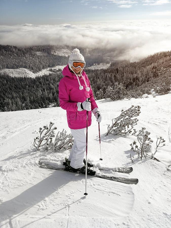 桃红色夹克、滑雪、滑雪杆、风镜和帽子的年轻女人,摆在积雪的滑雪道,发光对在她后的森林的太阳 免版税库存照片