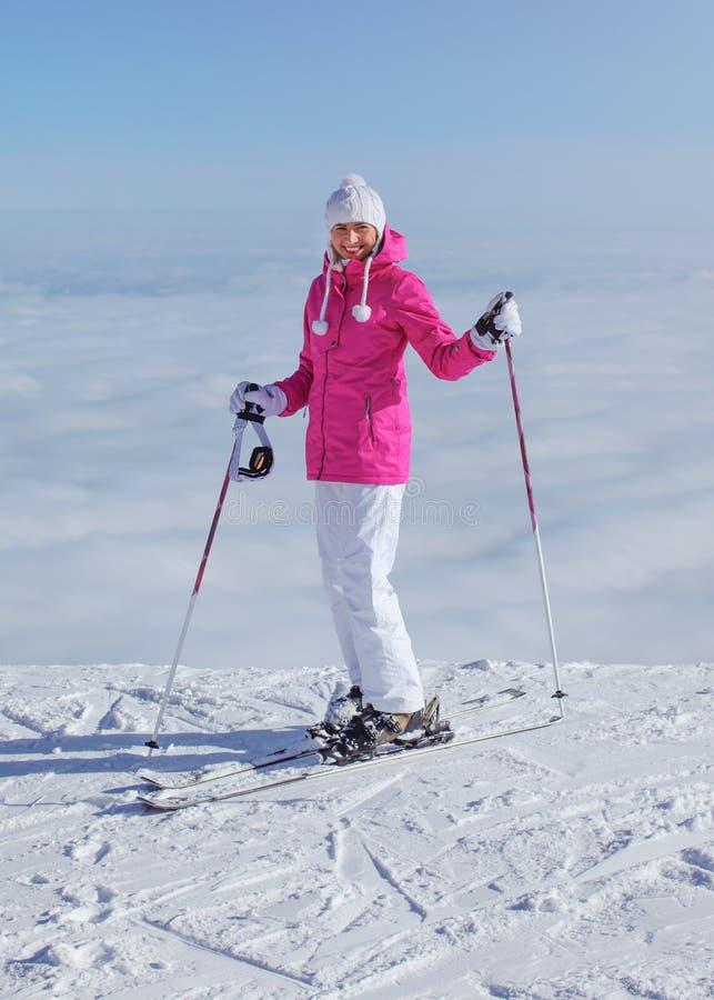 桃红色夹克、滑雪杆和滑雪的妇女,站立在小山边缘,下面只覆盖,回顾,微笑 库存图片