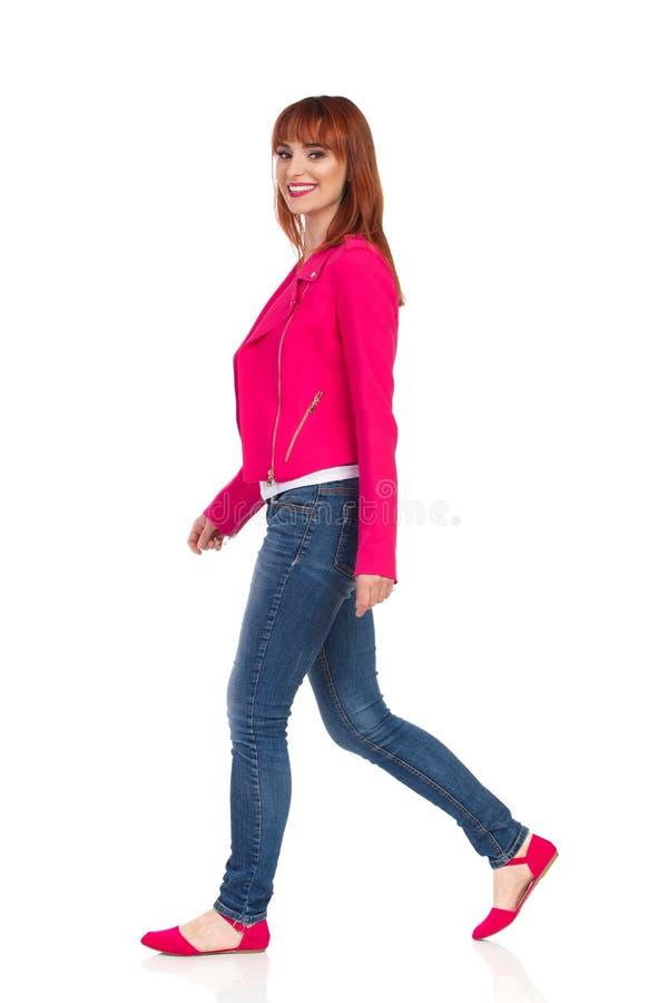 桃红色夹克和牛仔裤的走的年轻女人 库存照片