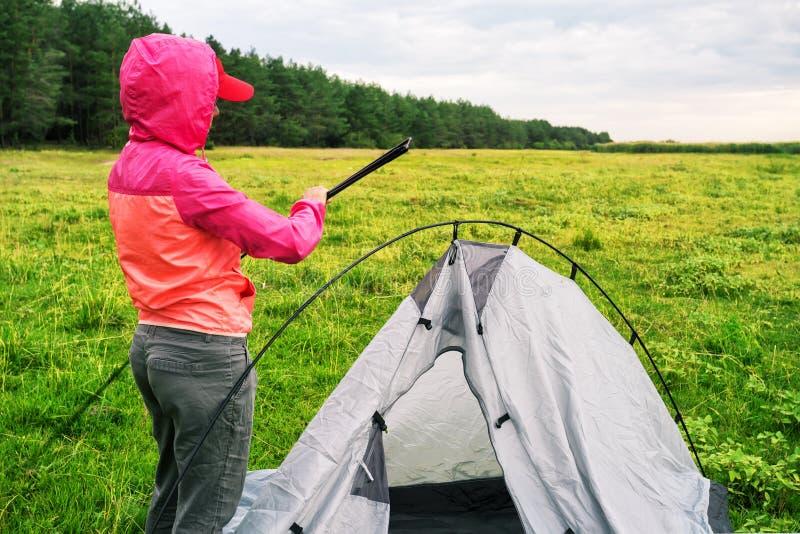 桃红色夹克的女孩有敞篷的设定了帐篷 库存图片