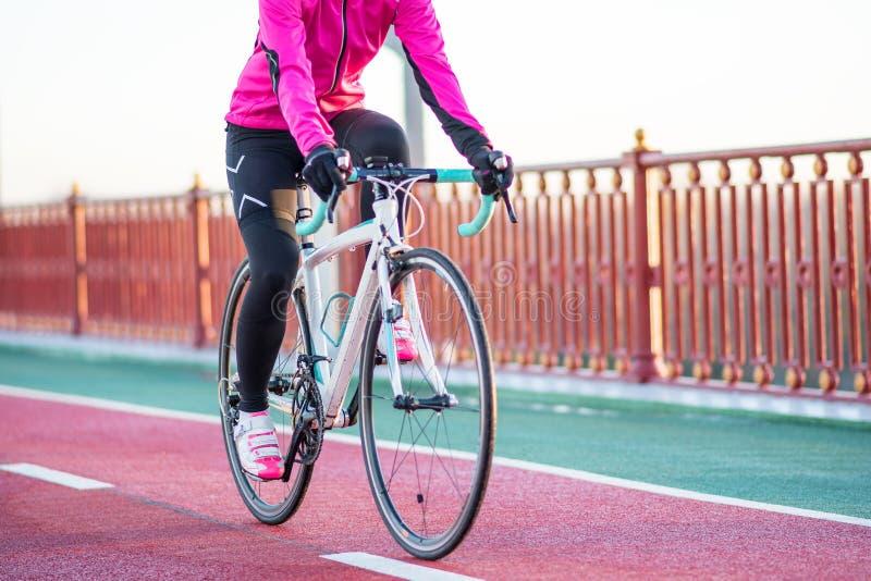桃红色夹克骑马路自行车的少妇在桥梁自行车线在冷的晴朗的秋天天 健康生活方式 免版税库存照片